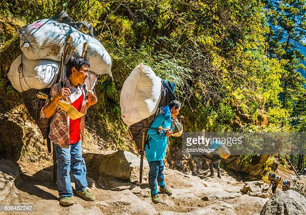 Sherpa porters carrying heavy basket on Everest trail Himalaya Nepal