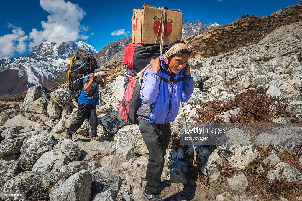 Sherpa Portieri di trasporto di carichi pesanti su sentiero di montagna Himalaya in Nepal : Foto stock