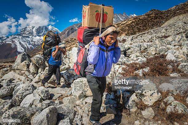シェルパポーター重い負荷にヒマラヤマウンテンコースネパール - 職業 ポーター ストックフォトと画像