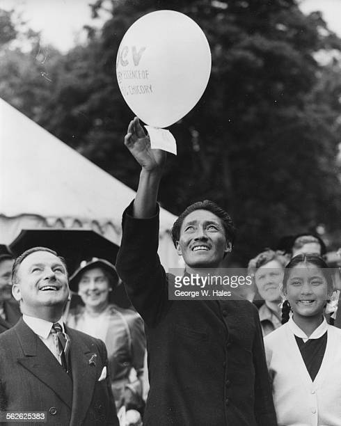 Sherpa Tenzing Norgay with his daughter Pem Pem releasing a balloon after returning from his successful Mount Everest expedition during a garden...