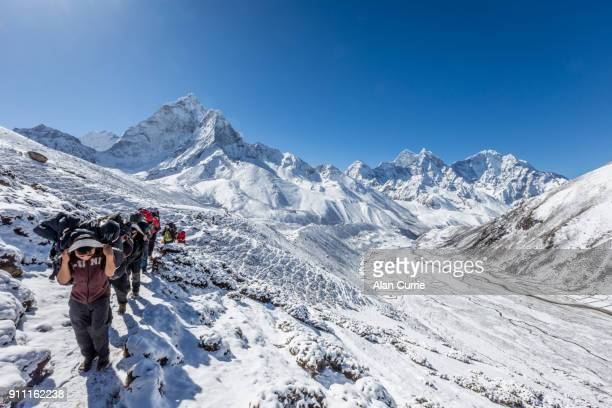 Sherpas and porters carrying luggage in the snow filled mountains of Nepal