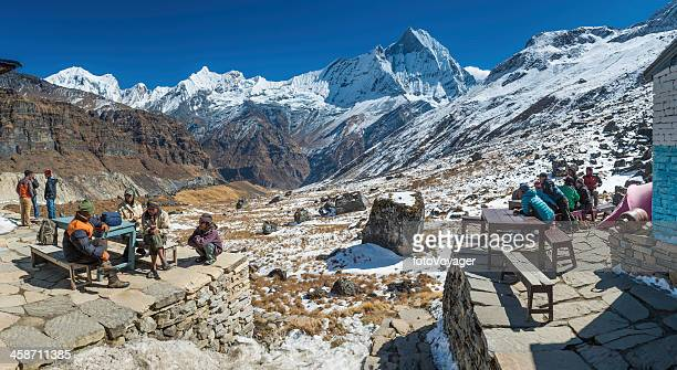 sherpas and porters relaxing at annapurna base camp himalayas nepal - annapurna conservation area stock photos and pictures
