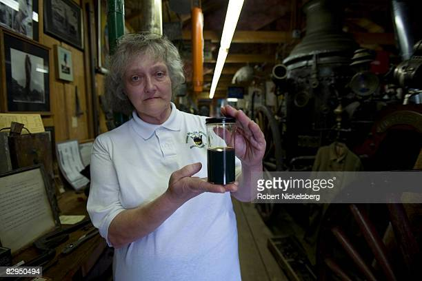 Sherri Schulze curator at the Penn Brad Oil Museum in Bradford Pennsylvania holds a jar of Bradford produced crude oil while standing next to an...