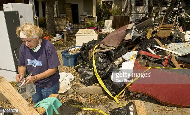 Sherrie Hoppal pauses from cleaning out her flooded home to sort through some family photographs that survived the high water from Hurricane Ike...
