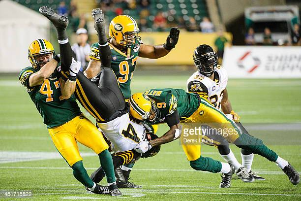 Sherritt and Patrick Watkins of the Edmonton Eskimos stop Bakari Grant of the Hamilton TigerCats during a CFL game at Commonwealth Stadium on July 4...
