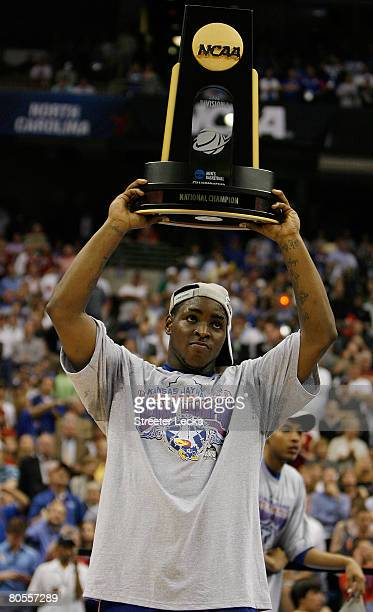 Sherron Collins of the Kansas Jayhawks celebrates by holdingup the championship trophy after defeating the Memphis Tigers 7568 in overtime during the...