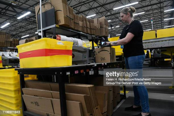 Sherry Betz packs items into small boxes at Amazon's Fulfillment Center on March 19 2019 in Thornton Colorado The facility which opened in July of...