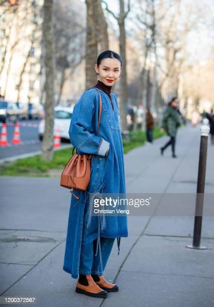 Sherry Shen is seen wearing denim cape, brown turteneck, bag, denim jeans outside Loewe during Paris Fashion Week - Menswear F/W 2020-2021 on January...