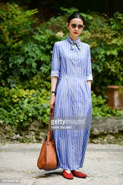 Sherry Shen poses wearing a 28.5 dress and Loewe bag before the Sunnei show during the Milan Men's Fashion Week Spring/Summer 2017 on June 19, 2016...