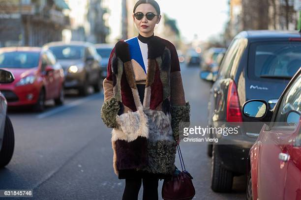 Sherry Shen wearing a Fendi fur coat knit bordeaux bag sunglasses at Etro during Milan Men's Fashion Week Fall/Winter 2017/18 on January 16 2017 in...