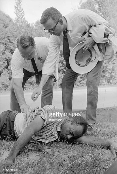 Sherwood Ross a Washington public relations advisor and an unidentified police officer examine the wounds of African American student James Meredith...
