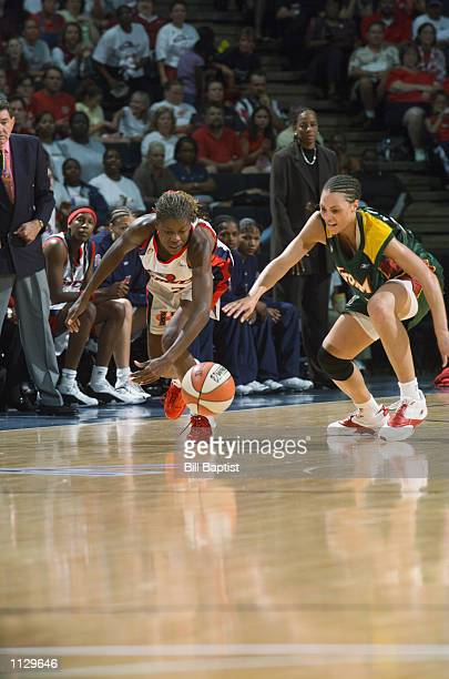 Sheryl Swoopes of the Houston Comets and Adia Barnes of the Seattle Storm scramble for a loose ball during the game on July 9 2002 at Compaq Center...
