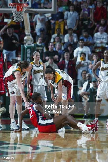 Sheryl Swoopes of the Houston Comets is helped up by Lauren Jackson and Adia Barnes of the Seattle Storm during the game on July 20 2002 at Key Arena...