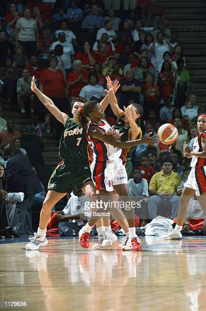 Sheryl Swoopes of the Houston Comets passes while under pressure from Adia Barnes and Kamila Vodichkova of the Seattle Storm during the game on July...