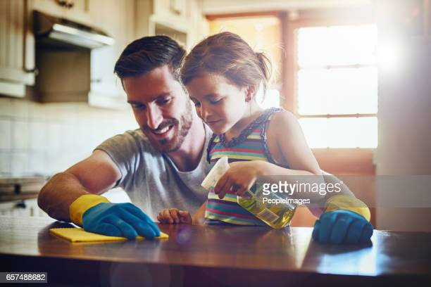 she's always willing to help dad get the housework done - clean stock pictures, royalty-free photos & images