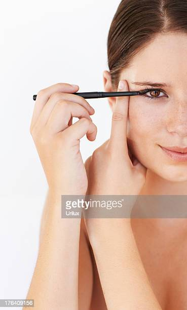 she's got the technique for applying makeup perfectly - eye liner stock pictures, royalty-free photos & images