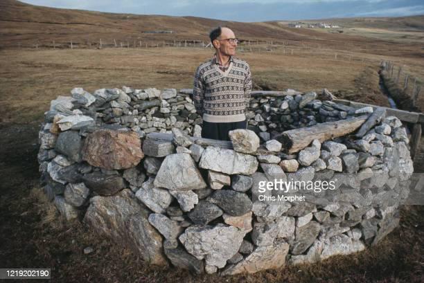 A Shetlander standing in a circular dry stone structure Shetland Islands Scotland June 1970
