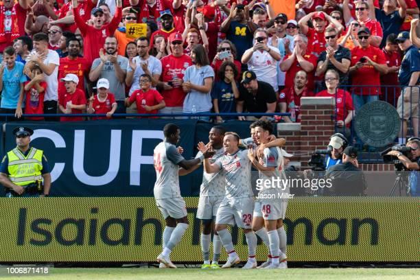 Sheyi Ojo celebrates with Xherdan Shaqiri and Curtis Jones of Liverpool after Xherdan Shaqiri scored the fourth goal against the Manchester United...