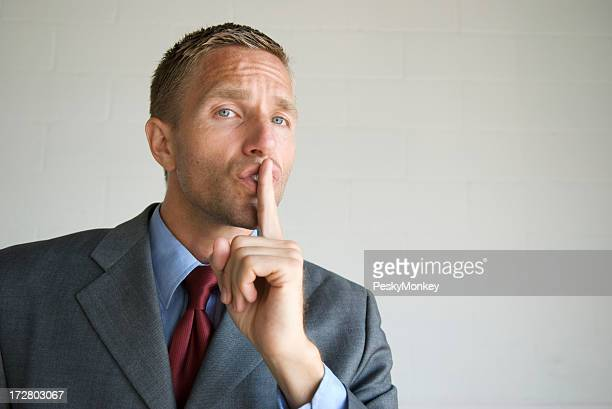 Shhh! Businessman Holding Finger to His Lips