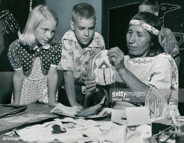 Shhh Indians At Work Watching intently as Mrs Alice Blackhorse stitches beadwork on a colorful Indian moccasin are Theresa Quinlan of 3358 Fillmore...