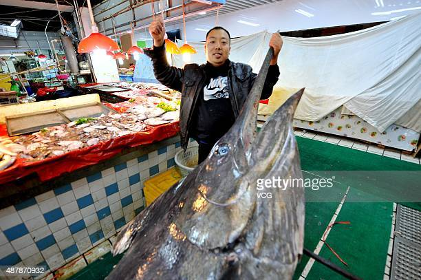 Shi Donglei owner of a wild seafood supermarket poses with a 310kilogram weight swordfish on September 12 2015 in Qingdao Shandong Province of China...