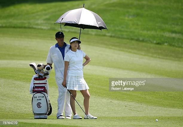 Shi Hyun Ahn of South Korea takes shelter from the sun under an umbrella held by her caddie on the 16th hole during the final round of the LPGA Kraft...