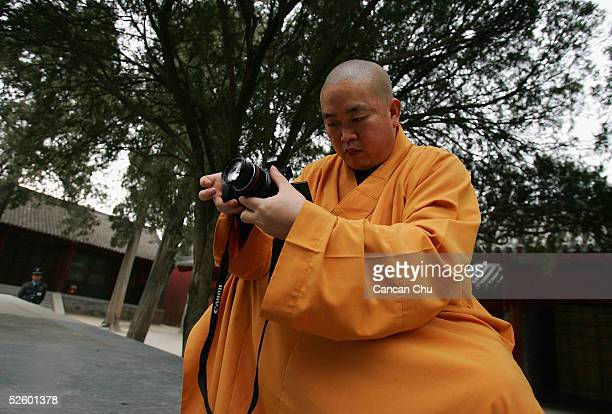 Shi Yongxin abbot of the Shaolin Temple takes pictures with a digital camera April 8 2005 in Dengfeng Henan Province China Shaolin Temple was built...