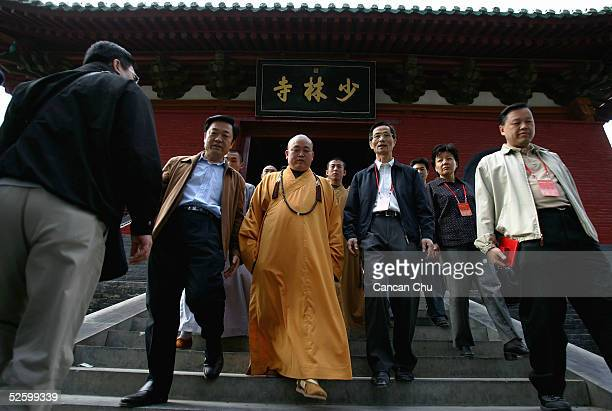 Shi Yongxin abbot of the Shaolin Temple walks out of the main gate of Shaolin Temple with tourists on April 7 2005 in Dengfeng Henan Province China...