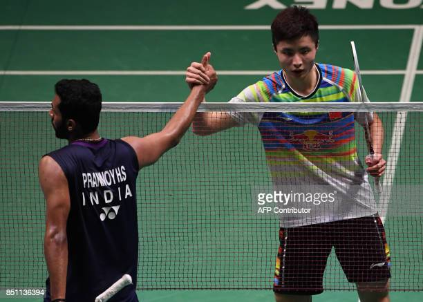 Shi Yuqi of China is congraturated by HS Prannoy of India during the men's singles quarterfinal match at the Japan Open Badminton Championships in...