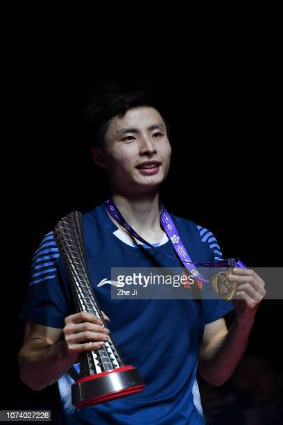 Shi Yuqi of China poses with his medal on the podium after defeating Kento Momota of Japan in the men's singles final match on day 5 of the HSBC BWF...