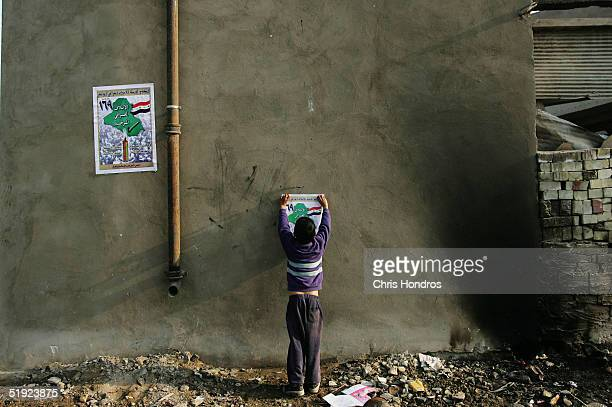 Shia boy pastes up campaign posters for the United Iraqi Alliance in the ethnically mixed al-Baladiyat neighborhood borhood January 7, 2005 in...