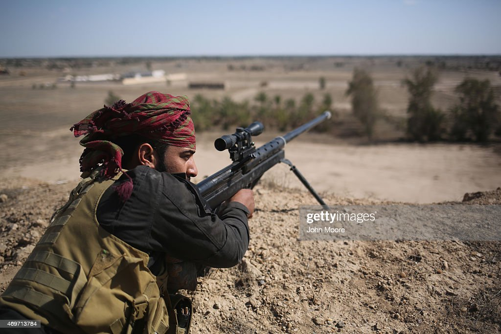 A Shia militia sniper from Abo al Fadhel al Abbas provides cover for Iraqi Army troops as they assault ISIL fighters on the frontline April 14, 2015 near Al-Karmah, in Anbar Province, Iraq. Shia militia forces continue to support the Iraqi Army as the government tries to push ISIL back from frontline positions in the predominantly Sunni area.
