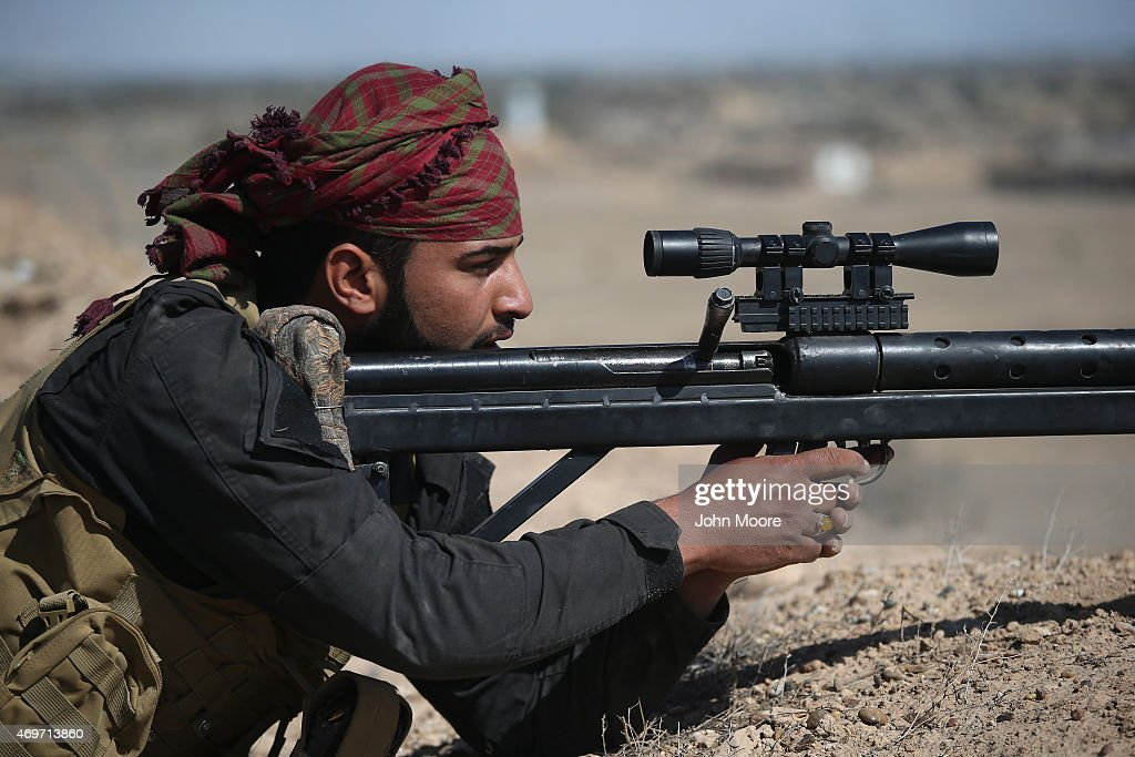 A Shia militia sniper from Abo al Fadhel al Abbas provides cover for Iraqi Army troops with an Iranian-made sniper rifle as forces assault ISIL fighters on the frontline April 14, 2015 near Al-Karmah, in Anbar Province, Iraq. Shia militia forces continue to support the Iraqi Army as the government tries to push ISIL back from frontline positions in the predominantly Sunni area.
