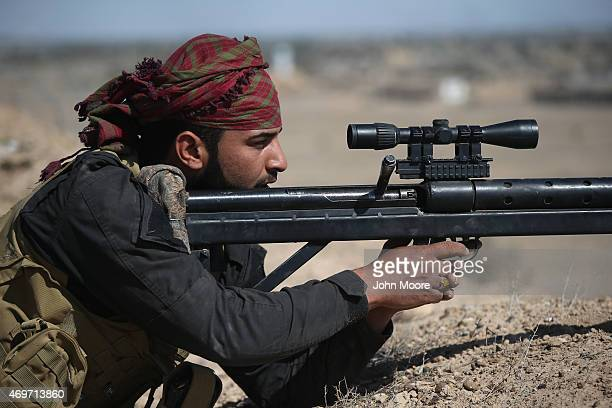 Shia militia sniper from Abo al Fadhel al Abbas provides cover for Iraqi Army troops with an Iranianmade sniper rifle as forces assault ISIL fighters...