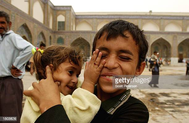 Shia Muslim Iraqi Brother And Sister Playfully Wrestle With Each Other During Friday Prayers At The