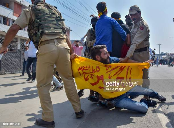 Shia Muslim mourner with a banner seen being dragged by the policemen after he took part in the Procession Police in Indian administered Kashmir...