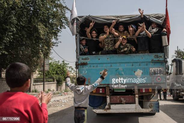 Shia volunteers cheer and wave from the back of a truck after delivering supplies to people as fighting continues against Islamic State in west...