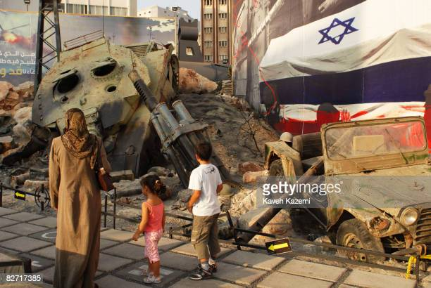 Shia woman in veil stands with her two children in front of an Israeli Markava tank and rocket launcher which was destroyed by Hezbollah forces in...