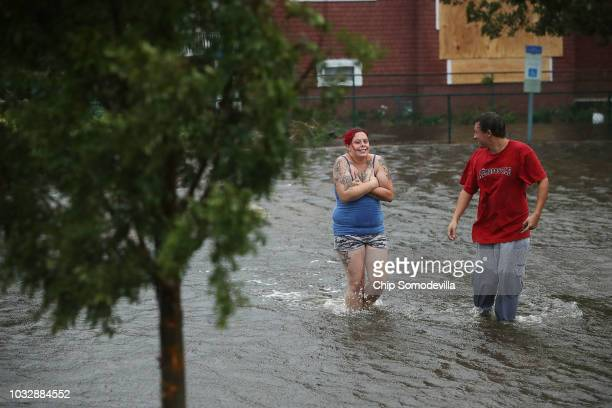 Shianne Coleman and Austin Gremmel walk in flooded streets as the Neuse River begins to flood its banks during Hurricane Florence September 13 2018...