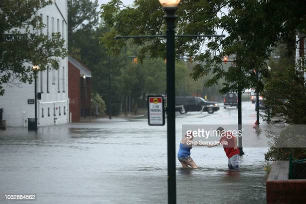 Shianne Coleman gets a hand from friend Austin Gremmel as they walk in flooded streets as the Neuse River begins to flood its banks during Hurricane...