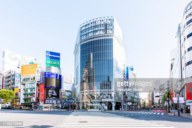 shibuya crossing on a sunny morning with clear blue sky, tokyo, japan - 横断する ストックフォトと画像
