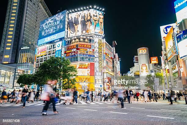 Shibuya crossing with illuminated neon signs at night, Tokyo, Japan