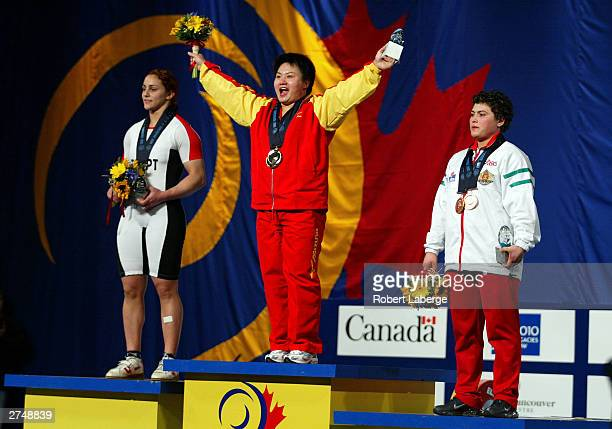 Shichun Shang of China on the podium as she accepts the Gold Medal for the combined Snatch and Clean and Jerk with Nahla Ramadan of Egypt silver...