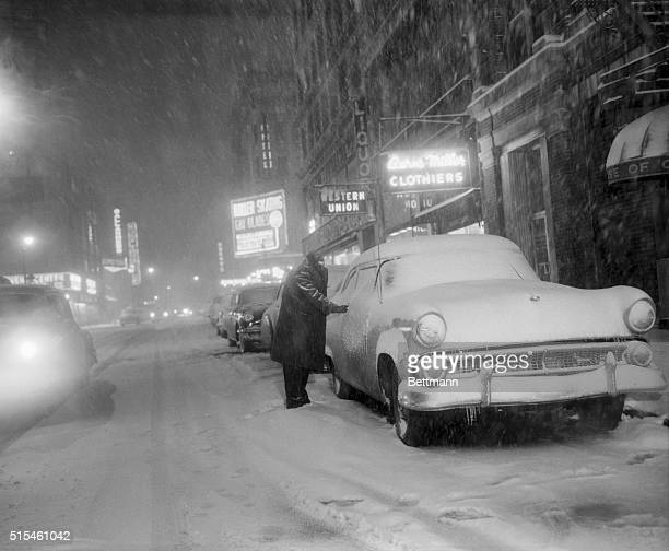 Shielding himself from the storm a driver has difficulty opening the door of his car whose lock has apparently frozen stiff in midtown Manhattan...