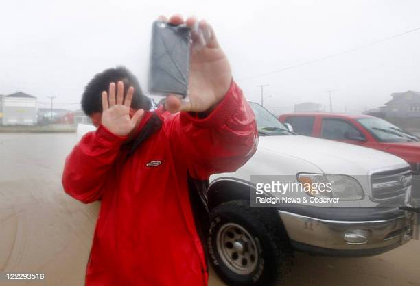 Shielding his eyes from the driving sand, Mike Scruggs takes a photo of the beach at Avalon Pier in Kill Devil Hills, North Carolina, during...