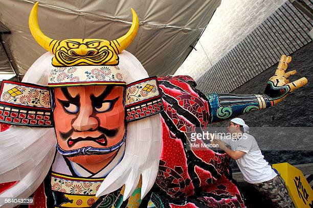 Shigeki Tezuka from Aomori Japan tests the lights on a nebuta float consisting of a massive samurai made of wire brightly painted paper and...