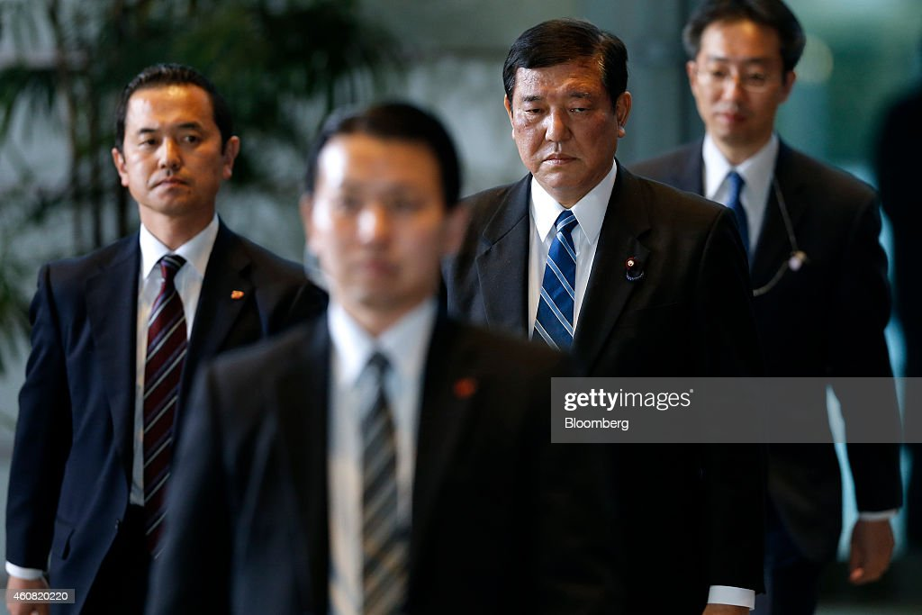 Shigeru Ishiba, Japan's re-appointed minister in charge of regional economy, second from right, arrives at the prime minister's official residence in Tokyo, Japan, on Wednesday, Dec. 24, 2014. Japanese Prime Minister Shinzo Abe appointed a former soldier and security veteran as his new defense minister, as he prepares to push through legislation to toughen the countrys military stance amid a dispute with China. Photographer: Kiyoshi Ota/Bloomberg via Getty Images
