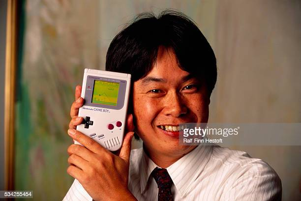 Shigeru Miyamoto, creator of Mario and other characters and video games for Nintendo, holds a Nintendo Game Boy containing the Super Mario World...