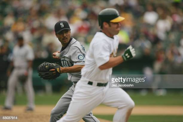 Shigetoshi Hasegawa of the Seattle Mariners prepares to throw to first base during the MLB game against the Oakland Athletics at McAfee Coliseum on...