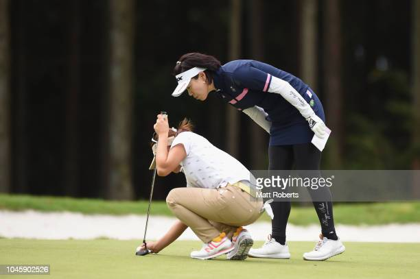 Shiho Oyama and Chie Arimura of Japan check the placement of the golf ball on the 4th green during the first round of the Stanley Ladies at Tomei...